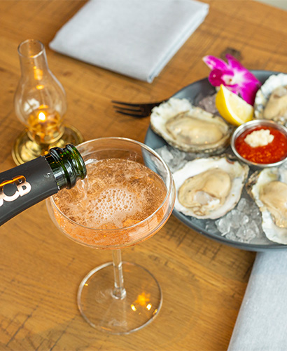 Champagne being poured into a glass with a tray of oyster in the background